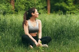 photo de jeune femme en tenue de sport assise sur l'herbe et se reposer dans le parc