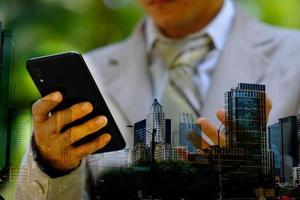 homme d'affaires utilisant un smartphone avec technologie, double exposition photo