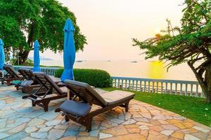 chaises de plage ou lits de piscine avec parasols autour de la piscine au coucher du soleil photo
