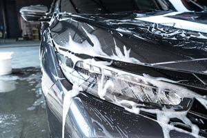 lampe de phare de voiture en gros plan avec mousse de lavage de voiture photo