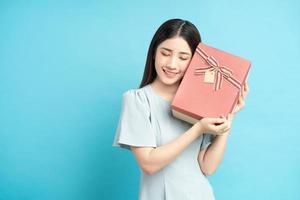 femme asiatique tenant une boîte-cadeau photo