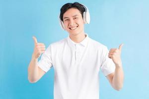 homme asiatique écoutant de la musique et utilisant ses pouces vers le haut photo