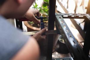 Faites-le vous-même concept, les artisans utilisent une pièce en forme de C pour assembler de vieilles pièces en fer. faire une étagère sur votre week-end libre photo