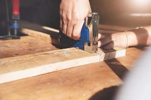 menuiserie d'entrepreneur tenant une agrafeuse pour assembler les pièces de bois comme le client l'a commandé. photo