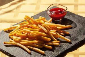 frites à la sauce tomate sur ardoise noire. frit, chips photo