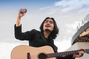 l'homme chante la chanson et joue de la guitare en plein air photo