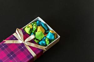 coffret cadeau coloré avec noeud en satin avec étoiles en papier origami sur fond noir. cadeaux pour les vacances. photo