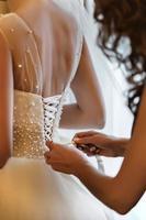 demoiselle d'honneur aidant la mariée à attacher le corset et à obtenir sa robe, préparant la mariée le matin pour le jour du mariage. rencontre de la mariée. photo