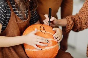 jeune fille assise à une table, décorant des citrouilles. vacances d'halloween et fond de style de vie familial. petite fille peint une citrouille pour halloween. mise au point sélective photo