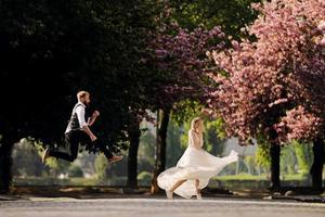 les couples de mariage heureux s'amusent dans le parc de sakura en fleurs de printemps. l'homme à la barbe saute, la femme en robe longue danse. couple nouvellement marié dans le parc. tout juste marié. mariage rustique. photo