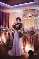 mariée heureuse avec un grand bouquet de roses. belle jeune mariée souriante détient un grand bouquet de mariage avec des roses roses. mariage dans des tons roses et verts. la cérémonie de mariage. photo