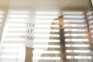 jeune femme dans un masque médical avec du papier avec des mots reste à la maison derrière une vitre à la maison. concept de quarantaine de la pandémie de coronavirus, covid 19. mise au point sélective photo