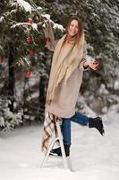 belle fille décore l'arbre de noël avec des boules rouges dans la forêt. bois d'hiver. l'hiver. joyeux Noël photo