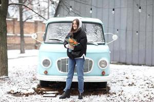 belle jeune femme s'amuse près de la voiture rétro bleue dans le parc d'hiver. fille tenant un bouquet de mandarines et d'épinettes fait avec ses mains. photo