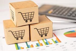 logo de panier d'achat sur la boîte avec calculatrice sur fond graphique. compte bancaire, économie de données de recherche analytique d'investissement, commerce, concept d'entreprise en ligne de transport d'importation d'exportation d'affaires. photo