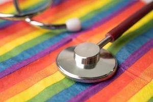 stéthoscope rouge sur fond de drapeau arc-en-ciel, symbole du mois de la fierté lgbt célèbre chaque année en juin social, symbole des gays, lesbiennes, bisexuels, transgenres, droits de l'homme et paix. photo