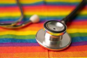 stéthoscope noir sur fond de drapeau arc-en-ciel, symbole du mois de la fierté lgbt célèbre chaque année en juin social, symbole des gays, lesbiennes, bisexuels, transgenres, droits de l'homme et paix. photo