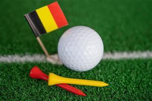 balle de golf avec drapeau allemand et tee sur pelouse verte ou herbe est le sport le plus populaire au monde. photo