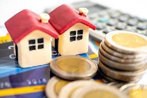 modèle de maison sur carte de crédit, pièce de monnaie et calculatrice, concept de paiement échelonné. photo