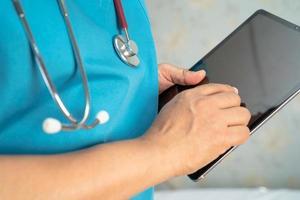 médecin tenant une tablette numérique pour rechercher des données pour traiter le patient dans un hôpital de soins infirmiers, concept médical solide et sain. photo
