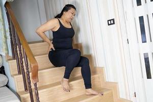 Une patiente asiatique d'âge moyen tombe dans les escaliers à cause de surfaces glissantes photo
