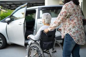 aidez et soutenez une patiente asiatique âgée ou âgée, assise sur un fauteuil roulant, se prépare à se rendre à sa voiture, concept médical solide et sain. photo