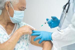 une femme âgée asiatique âgée portant un masque facial recevant un vaccin contre le covid-19 ou le coronavirus par un médecin fait une injection. photo