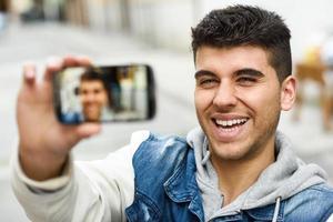 jeune homme selfie en arrière-plan urbain avec un smartphone photo