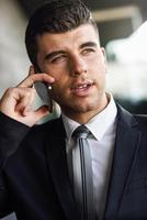 jeune homme d'affaires au téléphone dans un immeuble de bureaux photo