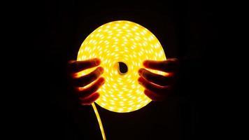 bobine de bande led rougeoyante avec une lumière chaude à la main photo