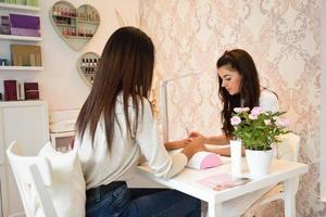manucure soins des ongles pour le client assis à une table au bureau. photo