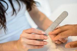 femme dans un salon de manucure recevant une manucure avec lime à ongles photo