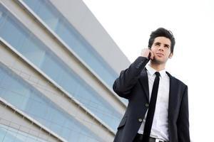 séduisant jeune homme d'affaires au téléphone dans un immeuble de bureaux photo