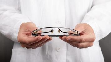 médecin ophtalmologiste tenant des lunettes, des béquilles pour les yeux photo
