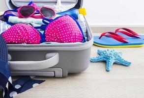 bikini rose et vêtements dans les bagages sur le sol stratifié photo
