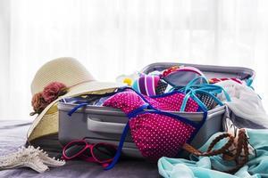 bikini rose et vêtements dans une valise sur le lit photo