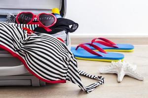 bikini et vêtements dans les bagages sur le sol stratifié photo