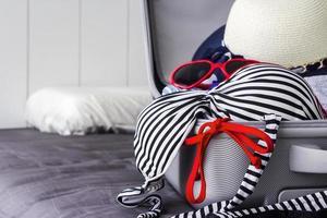 bikini et vêtements dans les bagages sur le lit photo