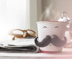 tasse avec une moustache sur une table en bois pour le concept de la fête des pères photo