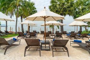 chaise de plage vide avec des palmiers sur la plage avec fond de mer photo