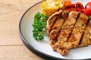 steak de porc grillé et grillé avec maïs, carottes et tomates photo