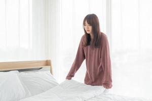 femme asiatique, faire lit, dans, chambre, à, blanc, drap propre photo