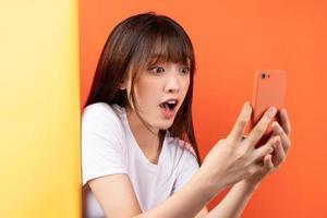 jeune fille asiatique qui se chevauchent sur fond jaune sur fond orange photo