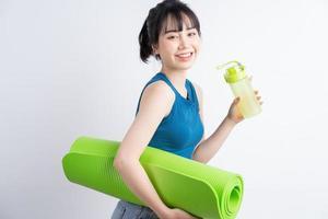belle fille asiatique portant un costume de yoga sur fond blanc photo