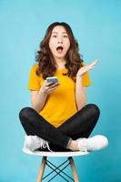 jeune femme asiatique assise sur une chaise à l'aide d'un téléphone avec une expression surprise photo