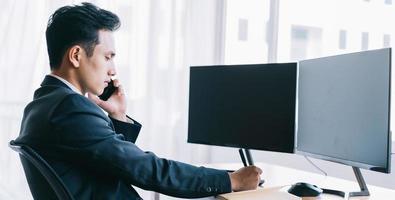 homme d'affaires asiatique concentré sur le travail au téléphone photo
