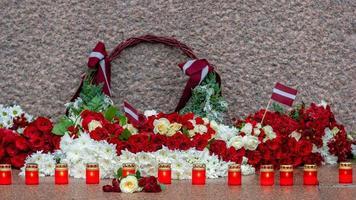 lettonie 100 ans. compositions de fleurs rouges et blanches au monument de la liberté dans la ville de riga, en lettonie photo