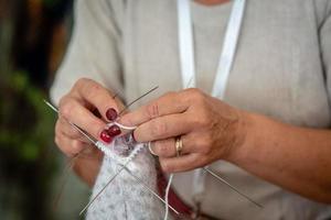 gros plan des mains d'une femme âgée tricotant. - image photo