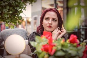 jeune femme rousse magnifique assise dans un café en plein air vêtue de vêtements de mode rétro. photo
