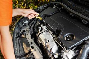 problèmes de voiture. la femme vérifie le niveau d'huile moteur. photo